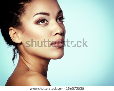 Beauty portrait of young mulatto fresh fashion woman with beautiful makeup, over blue - stock photo