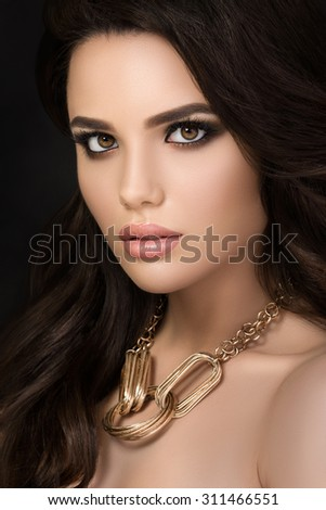 Beauty portrait of young pretty brunette girl wearing golden necklace - stock photo