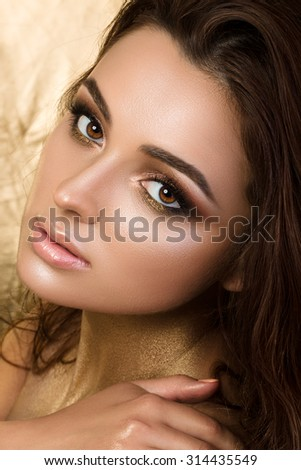 Beauty portrait of young pretty woman with fashion make-up. Bronzed skin and golden smokey eyes. - stock photo