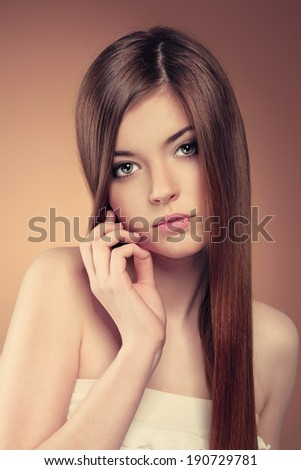 Beauty portrait of young sensual teenage girl with long straight brown hair. Pretty Caucasian female with professional makeup and hairstyle posing in studio.  - stock photo