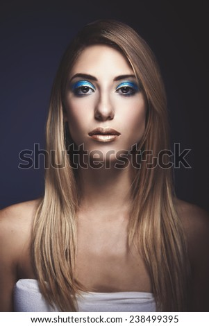 Beauty portrait of young sexy woman against blue background
