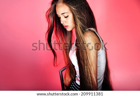 Beauty portrait of young teenage girl with long healthy hair. Studio shot, pink background. - stock photo