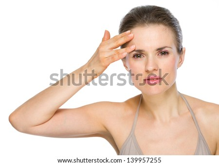 Beauty portrait of young woman checking facial skin - stock photo
