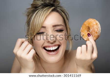 beauty portrait of young woman eating a sugar ring doughnut