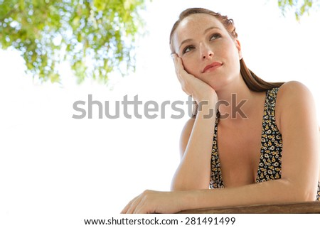 Beauty portrait of young woman leaning on a wooden banister balcony in a holiday home, relaxing and enjoying a summer day, outdoors. Healthy young woman being thoughtful against a sunny sky, exterior. - stock photo
