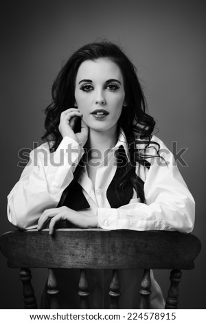 beauty portrait of young woman shot in the studio sitting on an old wooden chair