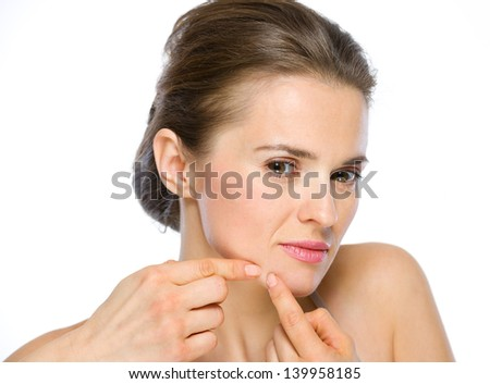 Beauty portrait of young woman squeezing acne - stock photo