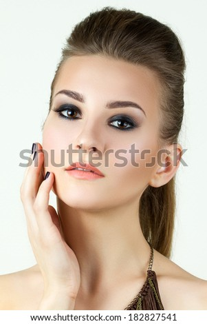 Beauty portrait of young woman touching her face - stock photo