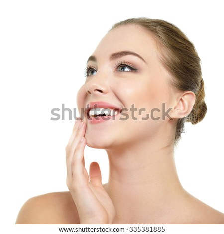 Beauty portrait of young woman touching her face, happy smiling and looking up, studio shot of attractive girl over white background