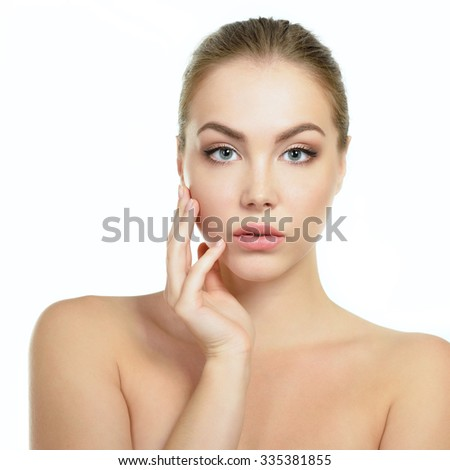 Beauty portrait of young woman touching her face with her fingers, studio shot of attractive girl over white background - stock photo