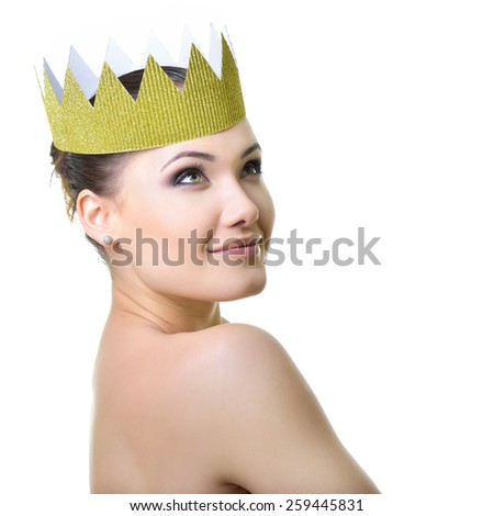 Beauty portrait of young woman with beautiful healthy face and crown, studio shot of attractive girl over white background - stock photo