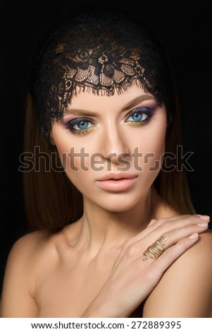 Beauty portrait of young woman with hand on her shoulder over dark background - stock photo
