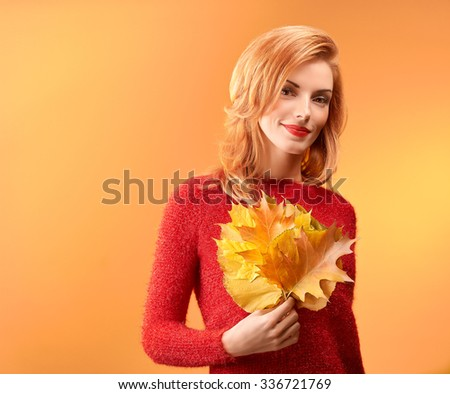 Beauty portrait redhead young model woman, autumn leafs in hands. Attractive happy playful girl in stylish red sweater smiling, people. Retro vintage, creative toned.Orange yellow background,copyspace - stock photo