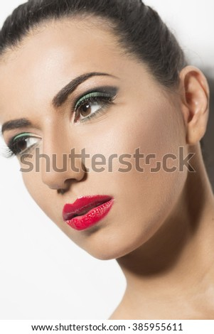 Beauty portrait with red lipstick and green eye shadow