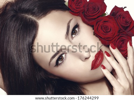 beauty portrait with red roses, lipstick and nail polish