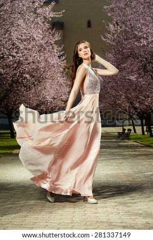 Beauty posing in luxury apparel outdoor in park - stock photo