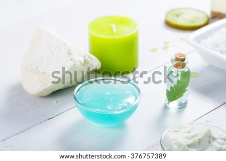 beauty products with kiwi fruit ingredient on white wooden table