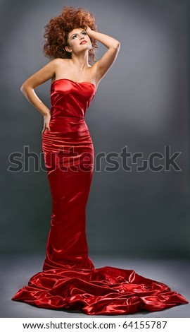 beauty redheaded girl in fashion dress on gray background - stock photo