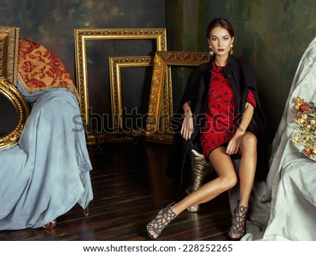 beauty rich brunette woman in luxury interior near empty frames, vintage elegance - stock photo