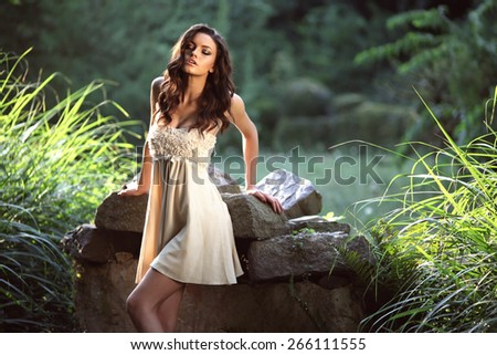 Beauty Romantic Girl Outdoors. Beautiful Teenage Model girl Dressed in Casual Short Dress on the park. Blowing Long Hair. Autumn. Glow Sun, Sunshine. Fashion colors. - stock photo