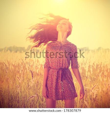 Beauty Romantic Girl Outdoors. Beautiful Teenage Model girl in Casual Short Dress on the Field in Sun Light. Blowing Long Hair. Autumn. Glow Sun, Sunshine. Backlit. Toned in warm colors - stock photo
