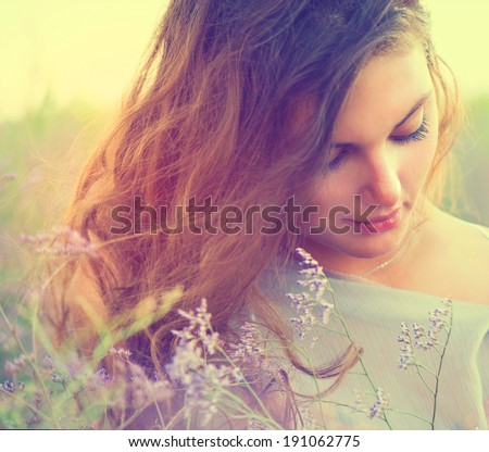 Beauty Romantic Girl Portrait. Sensual Woman Lying on a Meadow with Violet Flowers. Beautiful Woman Enjoying Nature. Romantic beauty in fantasy lavender field  - stock photo