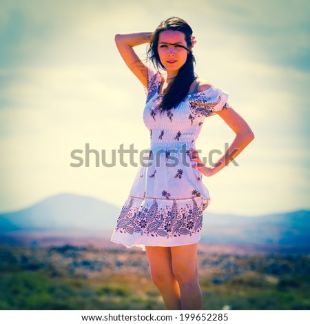 Beauty Romantic Young Girl Outdoors. Beautiful Teenage Model girl flowers Short Dress on the Mountain landscape in Sun Light. Brunette Long Hair. Summer. Glow Sun, Softfocus  - stock photo