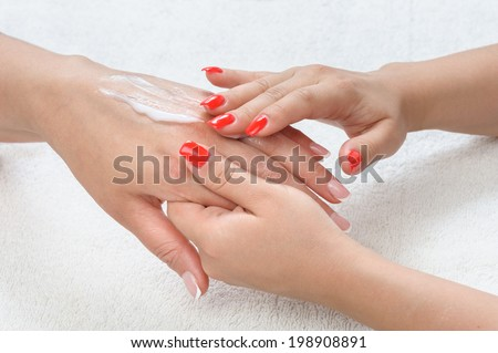 beauty salon, applying moisturizing cream onto the hands and massaging - stock photo