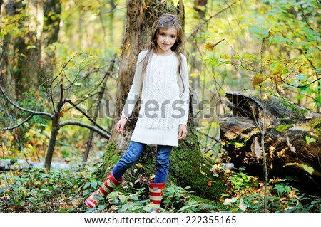 Beauty school aged brunette girl in white sweater and rain boots in the beauty autumn forest - stock photo