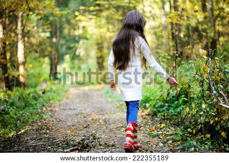Beauty school aged brunette girl in white sweater and rain boots in the beauty autumn forest. View from the back. - stock photo