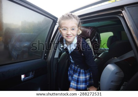 Beauty school aged kid girl in glasses and uniform near the car - stock photo