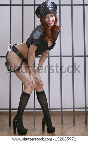 beauty sexy police woman on prison bar - stock photo
