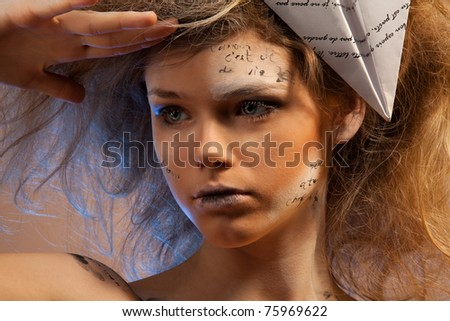Beauty shoot of a woman looking away holding her hand on elbow with words of love on her face and on paper plane  (words, printed on a plane was made up for this look)