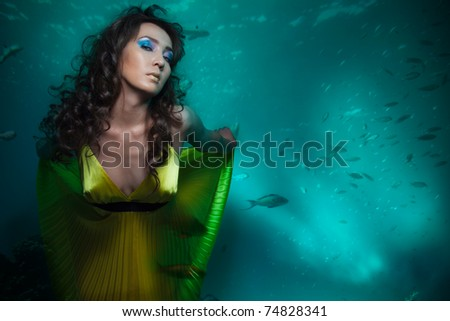 Beauty shoot of woman mermaid in yellow dress under the water - stock photo