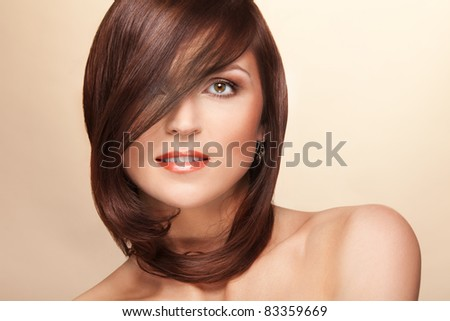 Beauty shoot of woman with hairs partly hiding face - stock photo