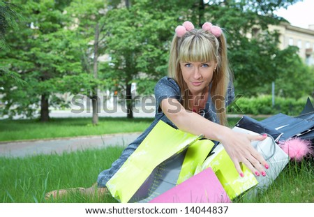 beauty shopping blonde girl on green grass with paper bag