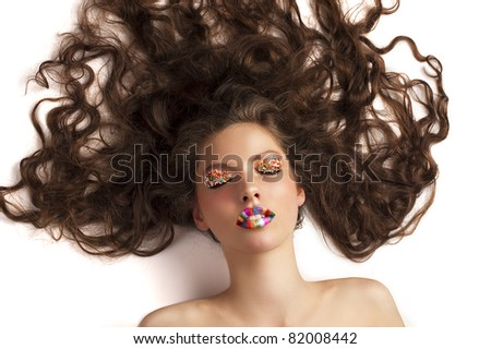 beauty shot of a laying girl with long hair spreaded around her head, candy make up on her eyes and rainbow lips