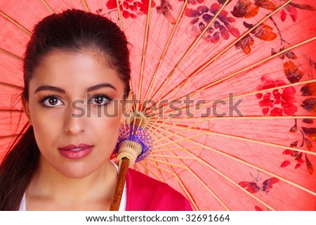 Beauty shot of a young brunette woman with brown eyes holding a red chinese umbrella - stock photo
