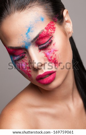 Beauty shot of fashionable womans face with pink, red and blue dry powder. red glitters on lips. FaceArt