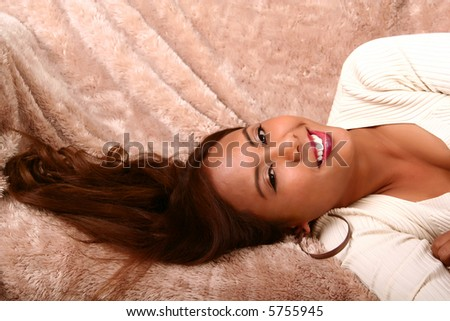 beauty shot of woman laying sideway on her bed showing happy expression