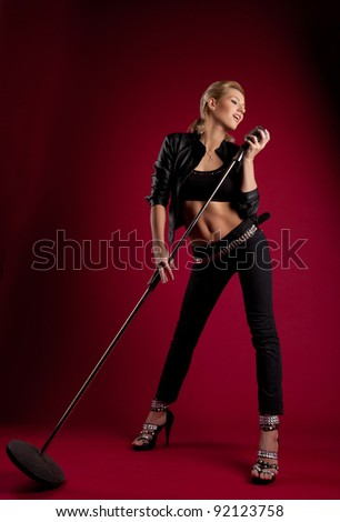 Beauty singer in black leather on red with mic