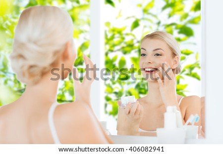 beauty, skin care and people concept - smiling young woman applying cream to face and looking to mirror at home bathroom over green natural background - stock photo