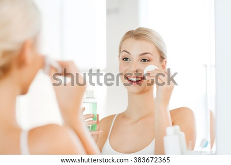 beauty, skin care and people concept - smiling young woman applying lotion to cotton disc for washing her face at bathroom - stock photo