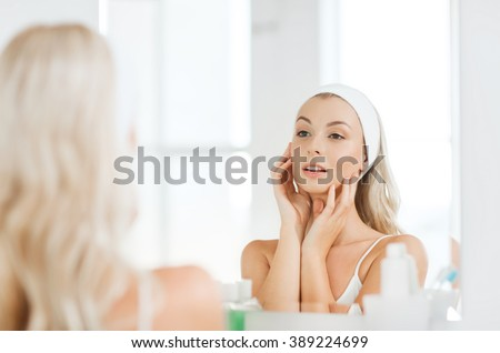 beauty, skin care and people concept - smiling young woman in hairband touching her face and looking to mirror at home bathroom - stock photo