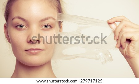 Beauty skin care cosmetics and health concept. Closeup young woman face, girl removing facial peel off mask on gray. Peeling - stock photo