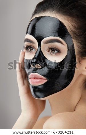 Beauty Skin Care Mask. Portrait Of Sexy Young Woman With Black Peel Mask On Face. Closeup Of Healthy Beautiful Female With Natural Makeup Applying Black Peeling Mask On Facial Skin. High Resolution