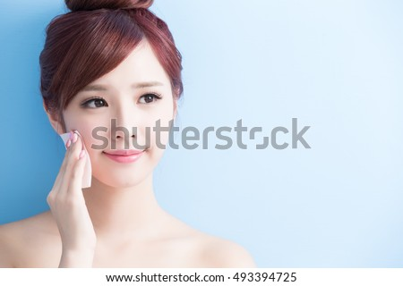 beauty skin care woman smile and make up on her face isolated on blue background, asian