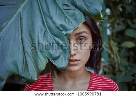 Beauty, skincare and natural cosmetics. Close up of beautiful young European female model with perfect skin posing among tropical plants, peeking out of big green leaf, advertising organic face lotion