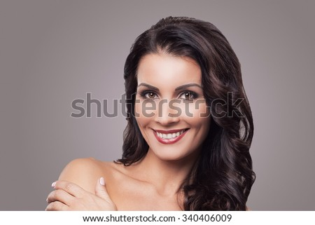 Beauty, skincare. Gorgeous brunette on a gray  background - stock photo