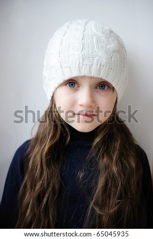 Beauty small girl with blue eyes and dark long hair in white knit hat